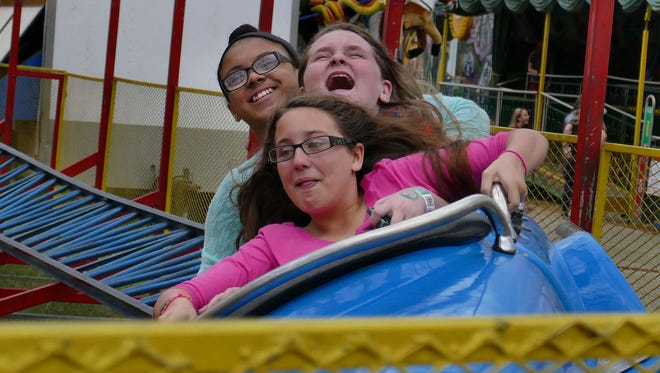 Front to back, Brianna Gray, 11, Lexy Coleman, 11, and Jessica Thomas, 13, make the thrilling final turn on the Indy 500 rollercoaster Oct. 25 at the Pensacola Interstate Fair.