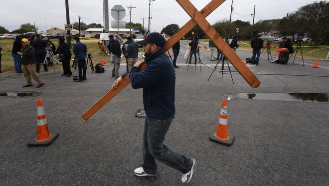 Joshua John Fitch carries a cross past the First Baptist Church which was the scene of the mass shooting that killed 26 people in Sutherland Springs, Texas on Nov. 8, 2017.