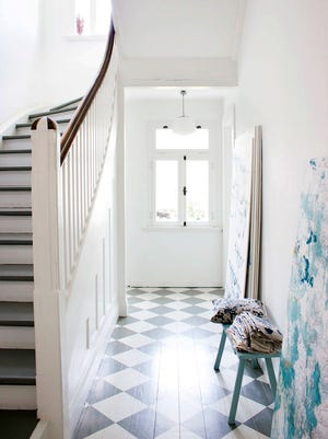 A white and gray checkerboard pattern painted on this hardwood floor brings the elegance of a tile floor to this otherwise casual, unpretentious hallway.
