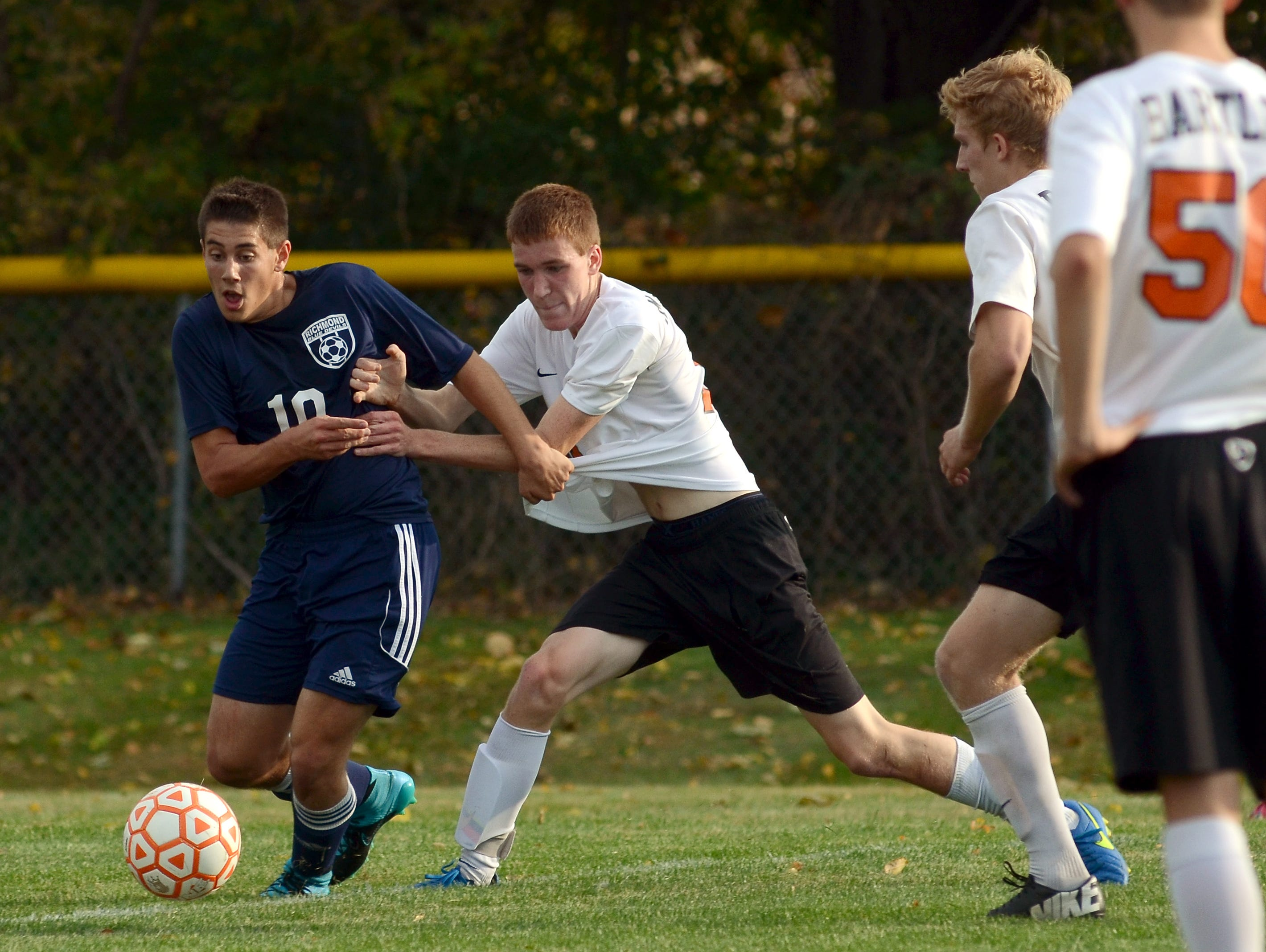 Richmonds' Matthew Schuster tries to keep Almonts' Zeck McCarthy away from the ball Monday, Oct. 12 during high school soccer action at Almont.