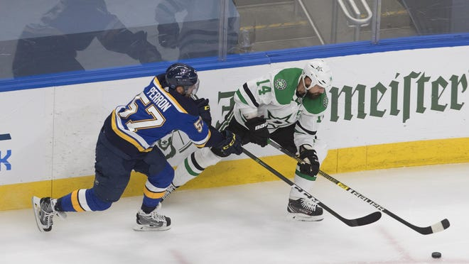 St. Louis Blues' David Perron (57) and Dallas Stars' Jamie Benn (14) battle for the puck during the second period of NHL qualifying round game in Edmonton, Alberta, on Sunday, Aug. 9, 2020.