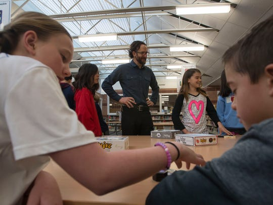 Olander Elementary teacher David Arnoff, center, discusses strategy with fifth graders Riley Mckay, center left, and Keolani Morrow, center right, while AJ Ziegler, left, and second grader Cruz Baca play a match of Hive, a bug-themed table-top strategy game, in a gifted and talented enrichment class on Friday, March 9, 2018, at Olander Elementary School in Fort Collins, Colo.