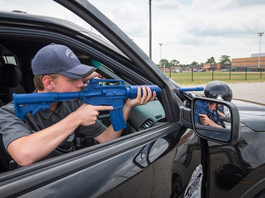 Gavin Sheehan, 16, holds a dummy rifle during a simulation of a high risk traffic stop Monday at the Port Huron Police School Youth Academy at Port Huron High School.