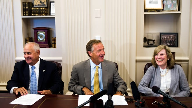 Tennessee Governor Bill Haslam, center, shares a chuckle with Deputy Gov. Jim Henry, left, and Commissioner Bonnie Hommrich, right, during press conference at the State Capitol in Nashville, Tenn., Tuesday, July 18, 2017.