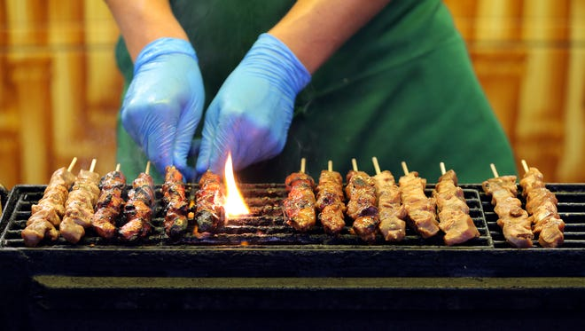 Kabobs are grilled to perfection at the Sati-Babi food booth on the midway at the Indiana State Fair on Monday, August 10, 2015.