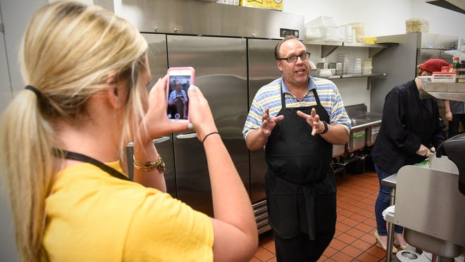 Paul Dols talks as his daughter Olivia records a video outlining the next day's specials to be posted to social media sites at Dolsie's Lunchbox Grille Wednesday, July 12, in downtown St. Cloud.