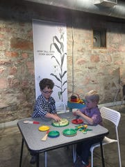 Grant Hoesing of Sioux Falls and Alex Peterson of Salem explore farm-to-table imaginative play at the site of the Stockyards Ag Experience Barn.