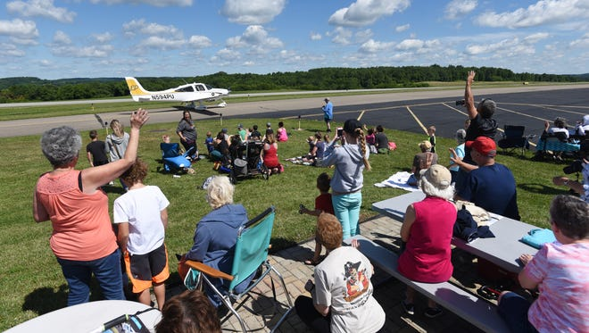 Visitors wave as the number 8 plane in the Air Race Classic taxis at Coshocton's Richard Downing Airport on Tuesday.