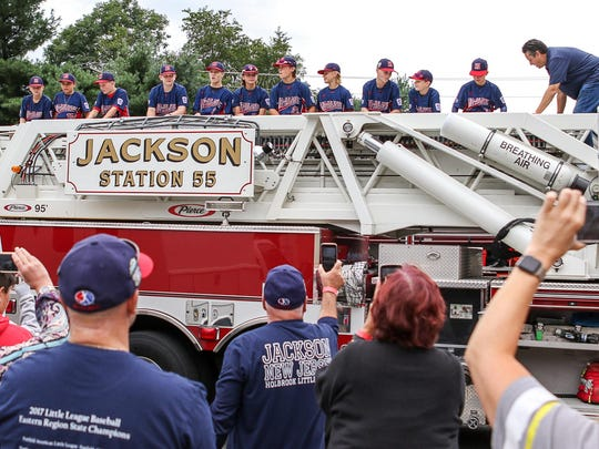 Holbrook Little League players stand on a firetruck from Jackson Station 55 at a celebration party sponsored by the Asbury Park Press, Knights of Columbus and Mona Lisa's Pizza on Saturday at the Knights of Columbus in Jackson.