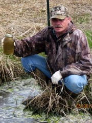 Terry Kafka, a runoff management specialist with the Department of Natural Resources, holds a water sample containing manure flowing from a farm field in Marathon County in 2014.