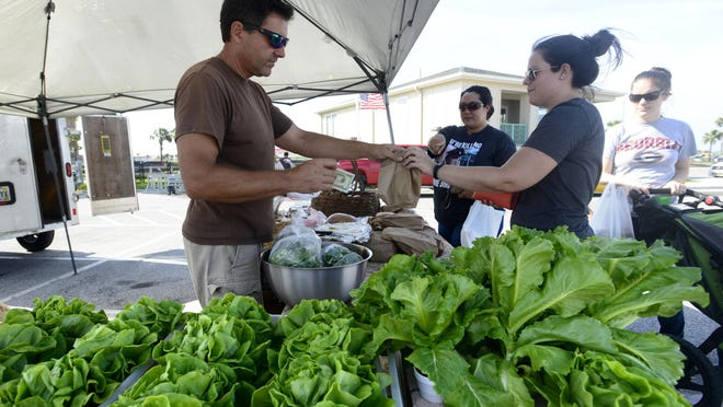 George Miller, with Miller Family Aquaponics, finishes a transaction with a customer Thursday at the Beach Market at the Casino Beach parking lot. The market will be open from 4-8 p.m. each Thursday.