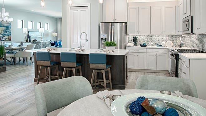 The Dolce model at Venetian Pointe features a kitchen with a café and a breakfast bar at the island counter.