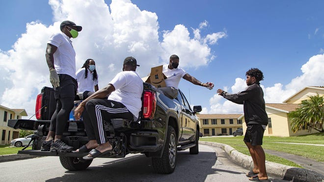 Jonathan Mann, right side of truck, hands out snacks on July 24 in Pahokee. With Mann, Glades football stars Deonte Thompson, left, Travis Benjamin and Jamal Miller (representing his best friend Pernell McPhee, who had to report to Baltimore Ravens training camp) formed JPDT Holdings to develop and improve the Glades area through business, economic, and community development projects.