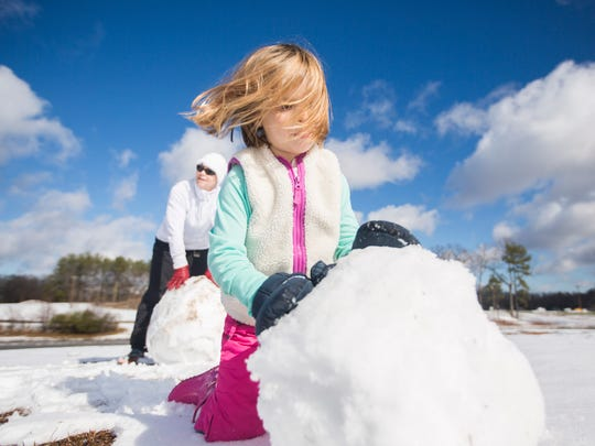 Myla Fletcher, 6, and her grandmother Jeryl Hollingsworth of Anderson work to make a snowman at Kite Hill on in Clemson.