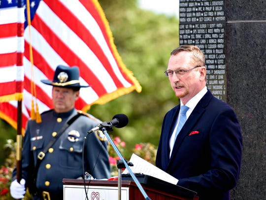 Deputy Steven Perkins, of the York County Sheriff's Office Honor Guard Team, left, secures the American flag as York County Department of Veterans Affairs Terry Gendron reads the 2016 names of honorees during the 2016 Court of Valor & Safekeepers Shrine Ceremony with York's Observance of the 15th Anniversary of 9/11 at Prospect Hill Cemetery in North York, Sunday, Sept. 11, 2016. Dawn J. Sagert photo