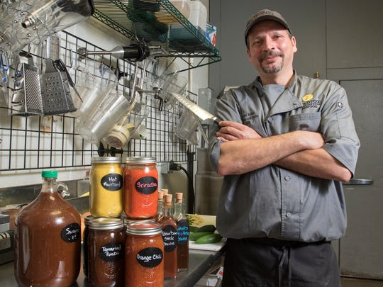 Chef Chris Kelly poses with some of the homemade sauces and condiments that he makes from scratch at his Ronin Sushi and Steak and Driftwood Bar and Grille restaurants at The Wharf in Orange Beach.