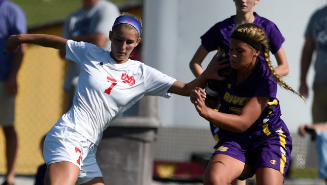 Sunny Lehman of Mater Dei battles for possession with Natalie Niehaus of Vincennes Rivet during the second half of the game at Boots Baumann Field in Evansville Saturday.  Mater Dei won 4-2 to capture the regional championship.