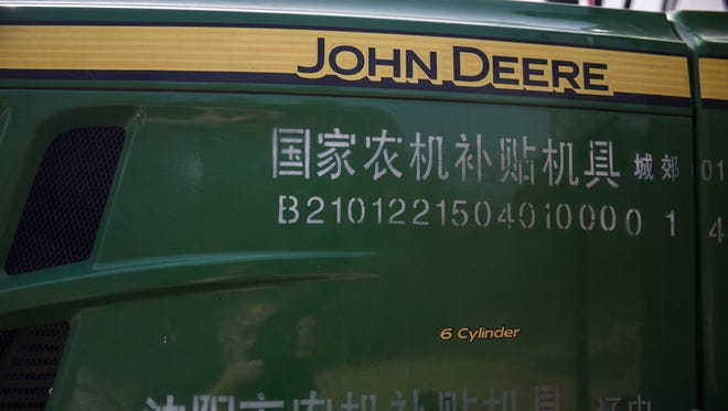 Mandarin characters accompany the English John Deere logo on a tractor set up for display during the groundbreaking of the China-U.S. Demonstration Farm on Saturday, Sept. 23, 2017, in Luanping County, Hebei, China.
