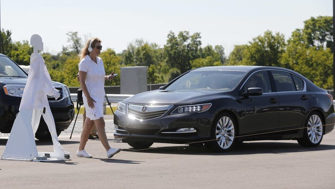 A pedestrian crosses in front of a vehicle as part of a demonstration at Mcity, used to test driverless and connected vehicles, on the University of Michigan campus in Ann Arbor, Mich., last July.