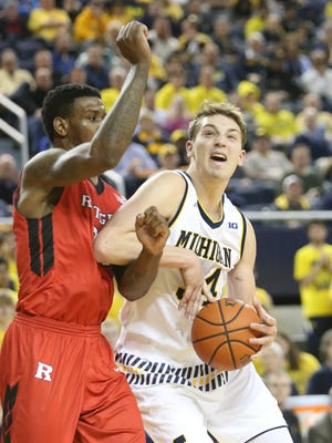 Michigan Wolverines Mark Donnal drives against the Rutgers Scarlet Knights Greg Lewis during second half action on Wednesday, January 27, 2016 at the Crisler Center in Ann Arbor, MI.