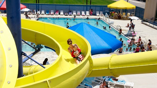 Tatiana Hare and her son, Dallin Hare, 2, descend one of the slides at the Bloomfield Family Aquatic Center on Tuesday as the area set records for high temperatures.