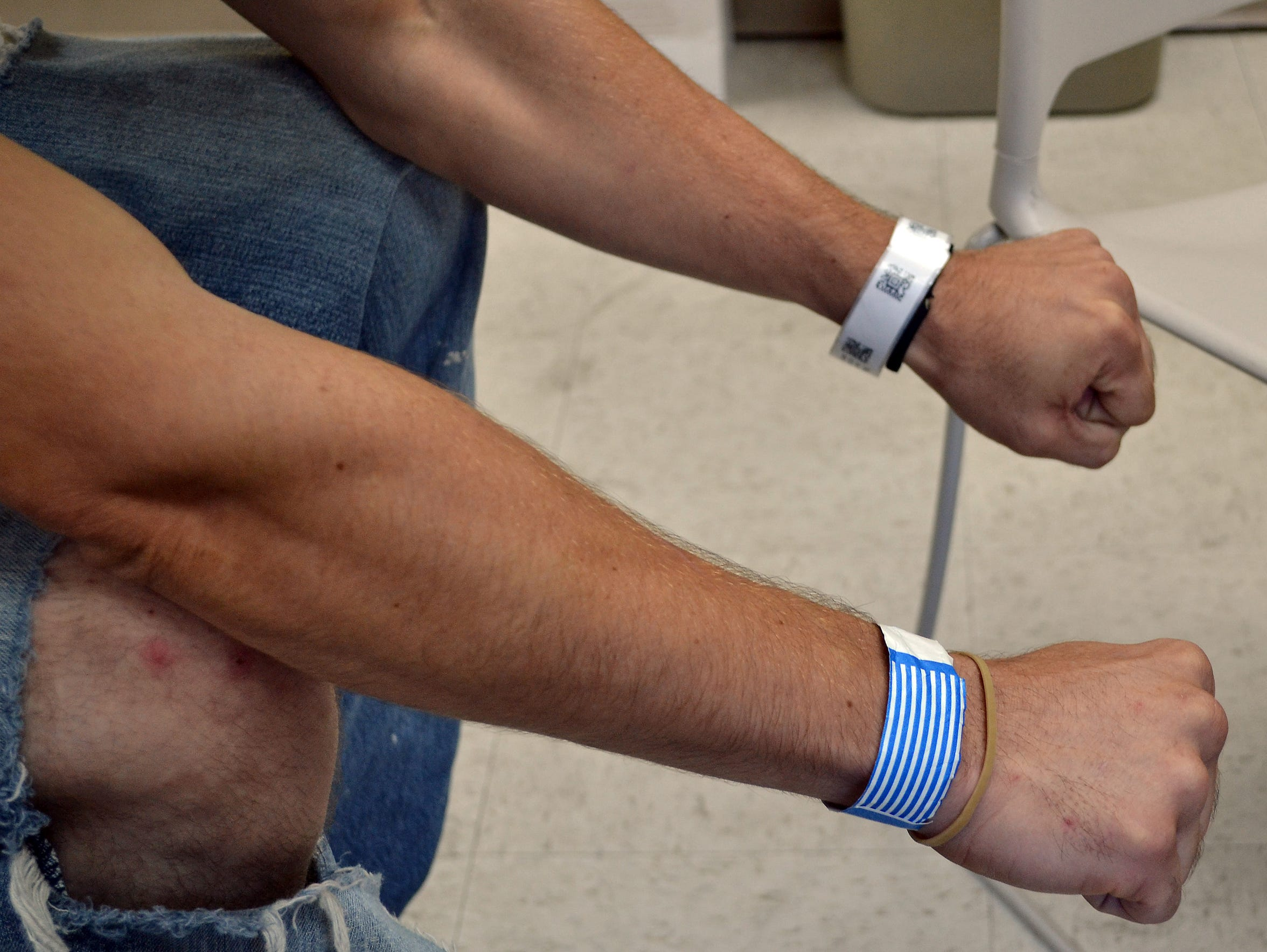A mobile crisis team client shows wristbands at the
