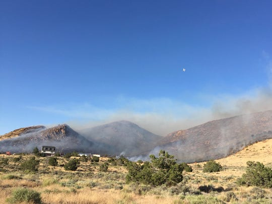 Fire raged around a home Tuesday evening near Pyramid Highway and Winnemucca Ranch Road. Planes dropped fire retardant as the fire spread up a nearby hillside. Flames were seen on the ridge going down into Palomino Valley on the other side, where a few crews observed the fire's progress.