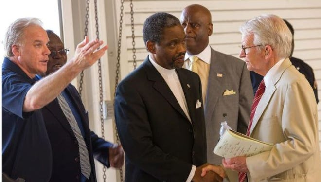 The Rev. Norvel Goff, center, is greeted by Charleston, Mayor Joe Riley, right, during a press conference Thursday, June 18, 2015, to announce the capture of Dylann Storm Roof, a white man who is suspected of killing nine people at a historic black church.