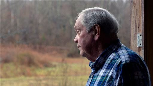 Larry Wilkins looks out in the direction of a plane crash Saturday in Kuttawa, Ky. A 7-year-old girl, the lone survivor of the crash, walked approximately three quarters of a mile through heavily overgrown woods to Wilkins' home, where he called for assistance.