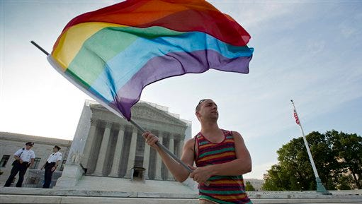 In this June 26, 2013 file photo, gay rights advocate Vin Testa waves a rainbow flag in front of the Supreme Court in Washington.