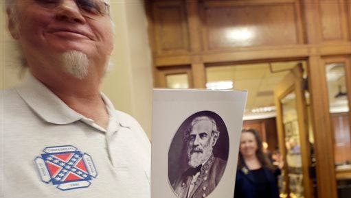 Dewey Spencer, of Judsonia, Ark., holds a portrait of Confederate Gen. Robert E. Lee after a meeting of the House Committee on State Agencies and Governmental Affairs, on Wednesday, Jan. 28, 2015, at the State Capitol in Little Rock, Ark. A bid to stop Arkansas' practice of commemorating Confederate Gen. Robert E. Lee and civil rights icon Martin Luther King Jr. on the same day failed before a state House panel.