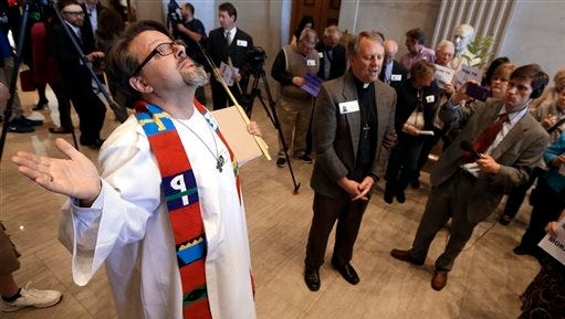 Rev. Brian Merritt, left, of the Justice and Peace Center in Chattanooga, Tenn., joins in a prayer outside the Senate chamber during a show of support for Gov. Bill Haslam's Insure Tennessee plan on Monday