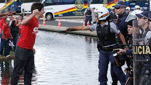 A demonstrator and a military police officer confront each other during a protest in Brasilia, Brazil, Tuesday, April 7, 2015. Thousands of workers have staged rallies in 12 cities across Brazil to protest against a proposed law that would allow companies to outsource their labor force. The biggest rally occurred in Brasilia where some 3,000 demonstrators gathered in front of Congress hours before lawmakers were expected to vote on the law. (AP Photo/Eraldo Peres)