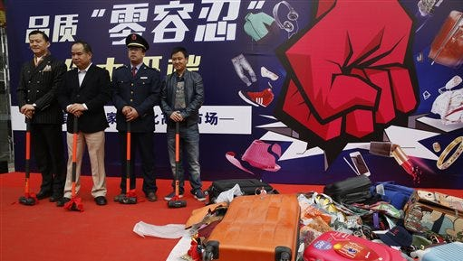 """In this Wednesday, April 8, 2015 photo, Chinese shop owners and government officials officiate at a ceremony to crack down on fake products outside the Silk Street market in Beijing. The words in Chinese read: """"Zero tolerance."""" China's top leadership has begun to take intellectual property protection seriously as it steers the economy away from low-end manufacturing toward innovation, but many critics say its courts are not yet up to the task. (AP Photo/Ng Han Guan)"""
