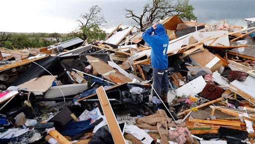 Jeff Stark looks over his home after a tornado ripped through Bridge Creek, Okla. on Wednesday, May 6, 2015.  Tornadoes hit Nebraska, Kansas, Oklahoma and north Texas on Wednesday. Most were small and chewed up only farmland, but a pair crossed into Oklahoma City and damaged homes and businesses. A few injuries were reported,  including about a dozen at an Oklahoma City trailer park and one woman drowned in an underground storm shelter that flooded.  (Steve Sisney/The Oklahoman via AP)LOCAL STATIONS OUT (KFOR, KOCO, KWTV, KOKH, KAUT OUT); LOCAL WEBSITES OUT; LOCAL PRINT OUT (EDMOND SUN OUT, OKLAHOMA GAZETTE OUT) TABLOIDS OUT