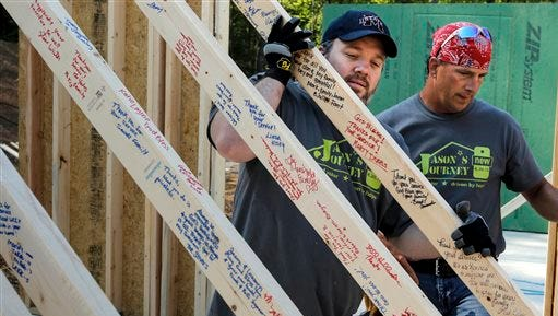 Volunteers Mike Easter, from Nashville, Tenn., left, and Shannon Crisp from Cleveland, Tenn., move an interior wall frame covered in messages from supporters and volunteers into place while constructing a new home for wounded U.S. Army veteran Jason Smith on Thursday, April 30, 2015, in Ringgold, Ga. Smith lost both of his legs in an IED explosion in Afghanistan in 2012, and the Steps 2 Hope Foundation has recruited volunteers from across the country to spend 9 days building Smith and his family a new home. (Doug Strickland/Chattanooga Times Free Press via AP)