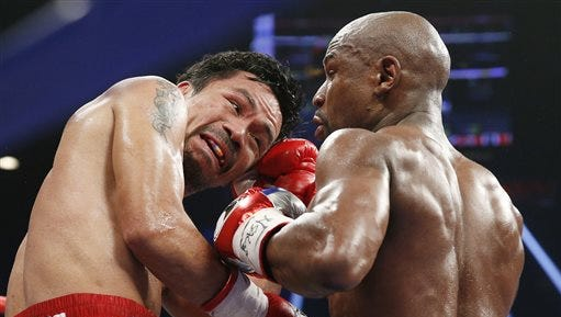 FILE - This May 2, 2015 file photo shows Manny Pacquiao, from the Philippines, left, trades punches with Floyd Mayweather Jr., during their welterweight title fight in Las Vegas. Boxing fans across the country or at least their lawyers are calling the hyped-up fight between Pacquiao and Mayweather a fraud. Some 31 class action lawsuits had been filed through Friday alleging primarily the same thing: that Pacquiao's pre-existing shoulder injury should have been disclosed to fans ahead of time.  (AP Photo/John Locher, File)