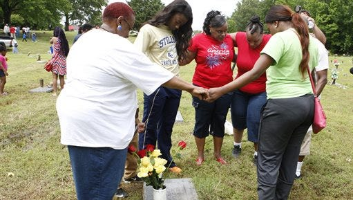 """Lula Warren, left, leads her family in prayer over the grave of her son, Alvin Walker Jr., on Monday, May 25, 2015, at the Galilee Memorial Gardens cemetery in Memphis, Tenn.""""I don't want to leave him,"""" she cried, after she was finally allowed inside the graveyard.  The cemetery was opened to visitors on Memorial Day after being closed after the cemetery owner was accused of burying multiple bodies in single graves by crushing and stacking caskets. (AP Photo/Karen Pulfer Focht)"""