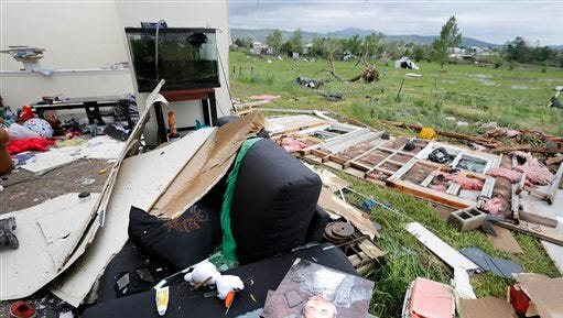 Debris is scattered in and outside a half-gutted home after the previous night's tornado, southwest of the town of Berthoud, Colo., Friday, June 5, 2015. A storm and a tornado that touched down in northern Colorado Thursday night damaged homes and brought flooding and marble-sized hail to some areas. (AP Photo/Brennan Linsley)