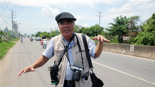 Pulitzer-winning photographer Nick Ut gestures while talking with media at the place where he took his iconic 'Napalm girl' photo 43 years ago on June 8 in Trang Bang, Vietnam.  Ut returned Monday to the location of his iconic photo with a tool from an entirely different era, a 4-ounce iPhone 5 equipped with the ability to send photos to the world in the blink of a digital eye.