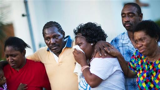 Gary and Aurelia Washington, center left and right, the son and granddaughter of Ethel Lance who died in Wednesday's shooting, leave a sidewalk memorial in front of Emanuel AME Church comforted by fellow family members Thursday in Charleston, South Carolina. Dylann Storm Roof, 21, was arrested Thursday in the slayings of several people, including the pastor at a prayer meeting inside the historic black church.