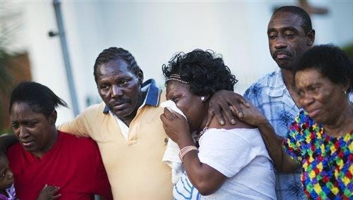 Gary and Aurelia Washington, center, left and right, the son and granddaughter of Ethel Lance who died in the Charleston church shooting, leave a sidewalk memorial in front of Emanuel AME Church comforted by fellow family members in Charleston, South Carolina.