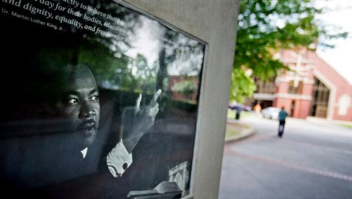 An image of Rev. Martin Luther King Jr., is displayed outside Ebenezer Baptist Church where Confederate flags were found on the premises Thursday, July 30, 2015, in Atlanta. U.S. authorities are investigating after several Confederate battle flags were discovered near the church and a civil rights center named after Martin Luther King, an iconic leader in the African-American Civil Rights Movement, Thursday morning. (AP Photo/David Goldman)