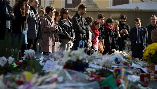 People mourn during a Europe-wide minute of silence to honor the victims of the terror attacks in Paris, in front of the French Embassy, in Rome, Monday, Nov. 16, 2015.