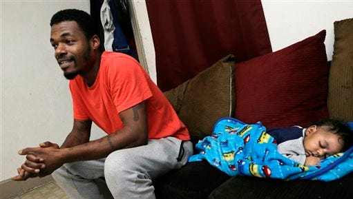 In this Wednesday, Nov. 25, 2015 photograph, Kareem Chappelle sits with his 2 month-old son Kwahli Chappelle, in their home in Philadelphia. When Chappelle forgot a court date, a bench warrant was issued, and Chappelle turned himself in the day before Thanksgiving. If he'd had $600 for bail, Chappelle could've gone home in time for the holiday. Instead, without the money, the first-time offender sat in jail for more than a month, missing Thanksgiving and Christmas with his girlfriend and two young sons. He also lost his home, his car and his job. (AP Photo/Mel Evans)