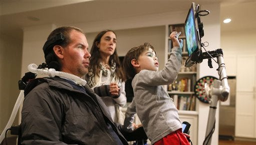 "In this Monday, Jan. 18, 2016, photo, former New Orleans Saints NFL football player Steve Gleason watches as his four-year-old son, Rivers, plays on his father's tablet as his wife, Michel, answers a question during an interview in their home in New Orleans. ""GLEASON,"" a feature-length documentary that gives an unfiltered look at his life with ALS premieres at the Sundance Film Festival on Saturday. (AP Photo/Jonathan Bachman)"