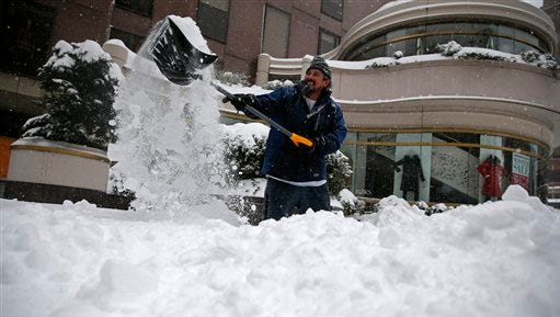Alfredo Milian shovels a walkway in downtown Washington, Saturday, Jan. 23, 2016. Millions of people awoke Saturday to heavy snow outside their doorsteps, strong winds that threatened to increase through the weekend, and largely empty roads as residents from the South to the Northeast heeded warnings to hunker down inside while a mammoth storm barreled across a large swath of the country. (AP Photo/Gerald Herbert)