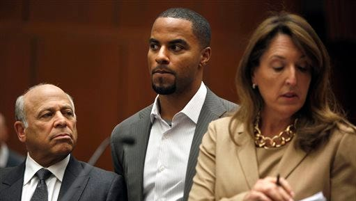 Former NFL football player Darren Sharper, center, appears in Los Angeles Superior Court with his attorneys, Blair Berk, right, and Leonard Levine in 2014.