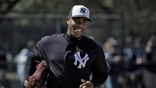 New York Yankees pitcher Aroldis Chapman smiles as he runs pickoff drills during a spring training baseball workout Friday, Feb. 19, 2016, in Tampa, Fla. (AP Photo/Chris O'Meara)
