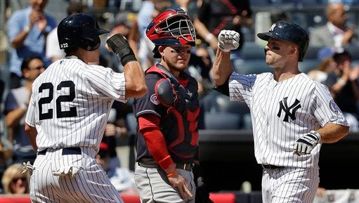 New York Yankees' Brett Gardner, right, is greeted at home plate by Yankees' Jacoby Ellsbury (22) as Cleveland Indians catcher Roberto Perez looks on after Gardner hit a two-run home run in the first inning of a baseball game, Saturday, Aug. 22, 2015, in New York.